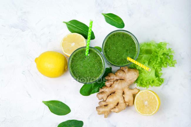 Очки из шпината с лимоном и имбирь зеленый коктейль на белой поверхности с ингредиентами — стоковое фото