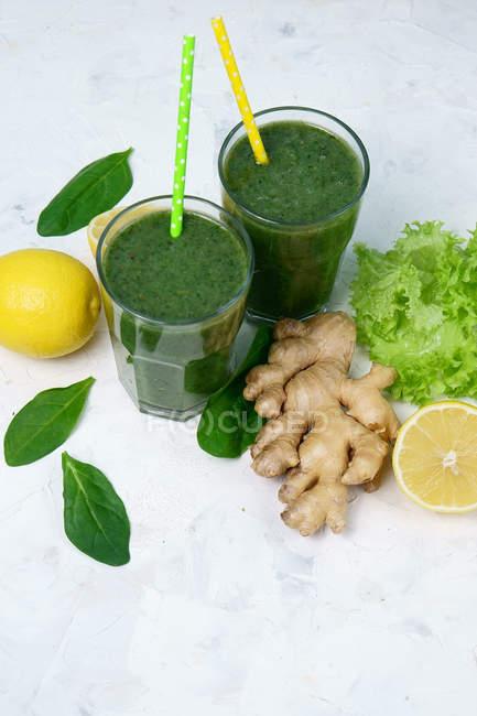 Copos de espinafre com limão e gengibre smoothie verde na superfície branca com ingredientes — Fotografia de Stock