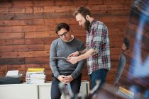 Male designers pointing at digital tablet — Stock Photo