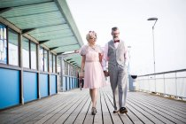 Couple strolling and holding hands on pier — Stock Photo