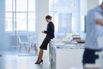 Businesswoman in office using mobile phone — Stock Photo