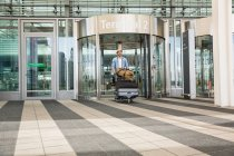 Man with luggage trolley arriving from airport — Stock Photo