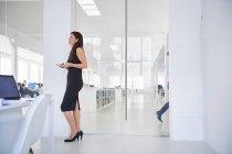 Бізнес-леді стоячи в офісі фотографіях хтось дивитися вбік — стокове фото