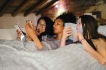Friends lying in bed looking at mobile phones — Stock Photo