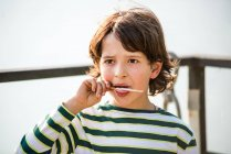 Boy finishing ice lolly in park — Stock Photo