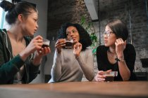 Friends drinking coffee at table — Stock Photo