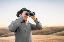 Man looking through binoculars — Stock Photo