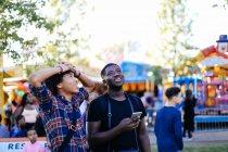 Dos amigos en el parque de atracciones - foto de stock