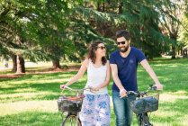 Couple strolling with bicycles in park — Stock Photo