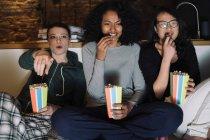 Friends on sofa eating popcorn — Stock Photo