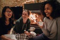 Друзья перед огнем пьют кофе — стоковое фото