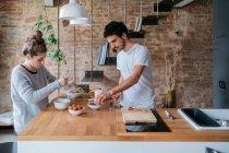 Couple preparing breakfast at kitchen counter — Stock Photo
