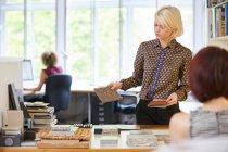 Female interior designer showing swatches — Stock Photo
