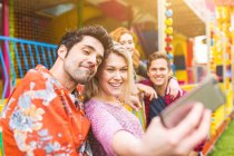 Group of friends taking selfie at fairground — Stock Photo