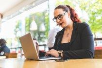 Giovane donna di affari che digita sul computer portatile — Foto stock