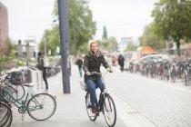 Studente in bicicletta dalla biblioteca — Foto stock