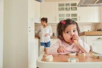 Bebé niña masticando números de juguete - foto de stock