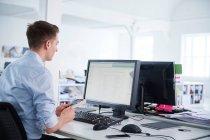 Homme au bureau utilisant un ordinateur — Photo de stock