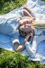 Пара лежит на одеяле для пикника в траве — стоковое фото
