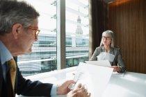 Uomo d'affari e donna d'affari, leggere e analizzare report — Foto stock