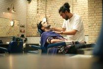 Hairdresser giving customer wet shave — Stock Photo