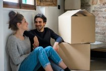 Couple sitting on floor by cardboard boxes — Stock Photo