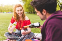 Man pouring champagne in park — Stock Photo