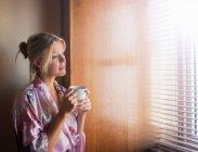 Young woman standing beside window — Stock Photo