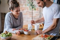 Couple eating fruit breakfast at counter — Stock Photo