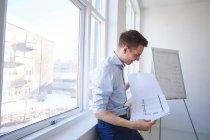Architecte au bureau regardant le plan directeur — Photo de stock