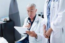 Arzt schaut sich medizinische Diagramme an — Stockfoto