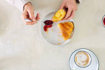 Donna che mangia croissant e marmellate — Foto stock