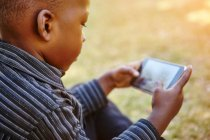 Boy playing game on cellular phone — Stock Photo
