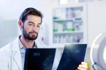 Medico che esamina immagine dei raggi x — Foto stock