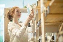 Femme ramassant le produit de l'étagère — Photo de stock