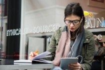 Junge Frau schaut auf digitales Tablet — Stockfoto