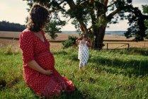 Femme enceinte regardant bambin fille — Photo de stock