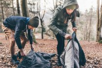 Hiking couple packing sleeping bags — Stock Photo