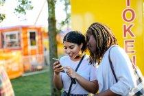 Due ragazze al luna park, guardando smartphone — Foto stock