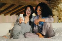 Friends sitting on bed and looking at smartphone — Stock Photo