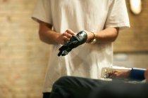 Hairdresser putting on latex glove — Stock Photo
