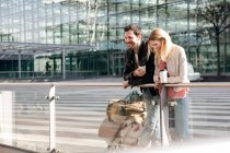 Couple with coffee and baggage trolley — Stock Photo