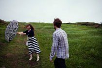 Couple standing in field on windy day — Stock Photo
