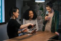 Друзі обміну пляшка червоного вина — стокове фото