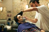 Parrucchiere dando cliente rasatura bagnata — Foto stock