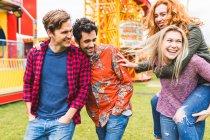 Grupo de amigos caminhando no parque de diversões — Fotografia de Stock