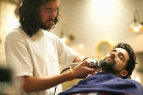 Hairdresser shaving customers beard — Stock Photo