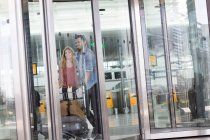 Couple with luggage trolley in airport terminal — Stock Photo