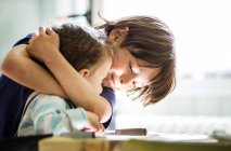 Boy at table hugging toddler brother — Stock Photo