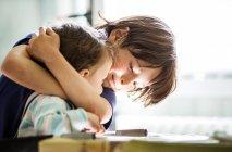 Junge am Tisch umarmt Kleinkind Bruder — Stockfoto